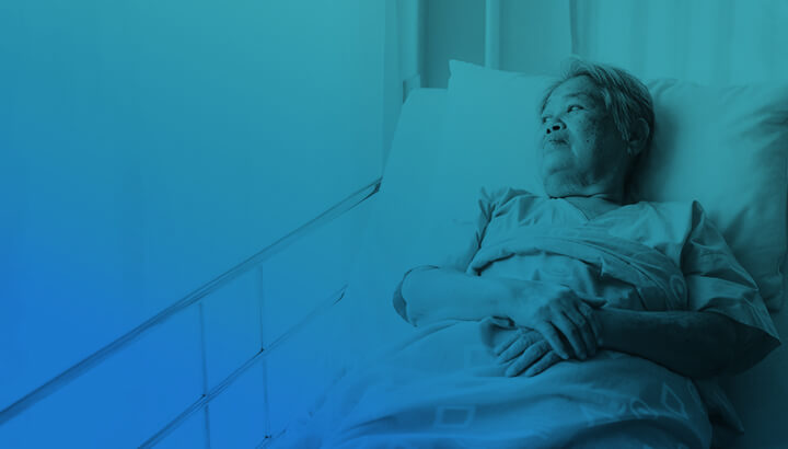 Elderly Asian woman with white hair laying in nursing home bed with hands folded gazing out the window